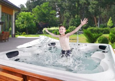 A happy boy jumping in the Arctic Spas Hot Tub