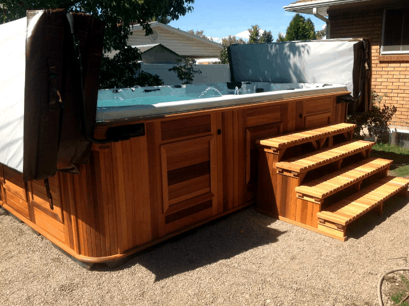 Arctic Spas Swim Spa with open covers in the backyard